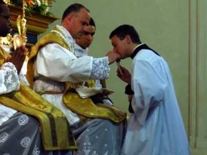 Jeden z kleryków przyjmuje z rąk ks. Pagliaraniego medal z wizerunkiem św. Piusa X