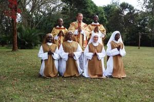 Ks. A. M. Nely FSSPX z asystującymi diakonem i subdiakonem oraz siostrami, które złożyły przyrzeczenia i przyjęły habity