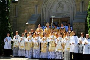 Bp de Mallerais w otoczeniu nowo wyświeconych diakonów i kapłanów oraz asysty liturgicznej przed kaplicą seminarium w Winonie